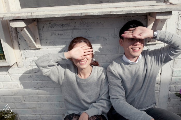 Shading the sun from their eyes with their hands this Malaysia couple poses During their pre-wedding portrait session
