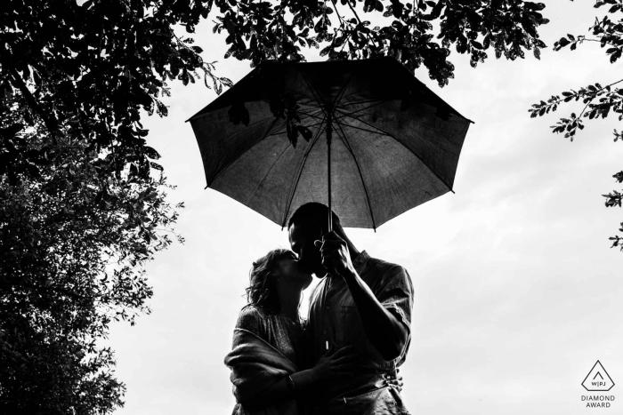 Portrait de fiançailles Nouvelle-Aquitaine sous les arbres et abrité par un parapluie