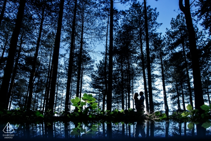 Silhouette of couple hugging in the forest with deep blue skies in the background | England Photographer