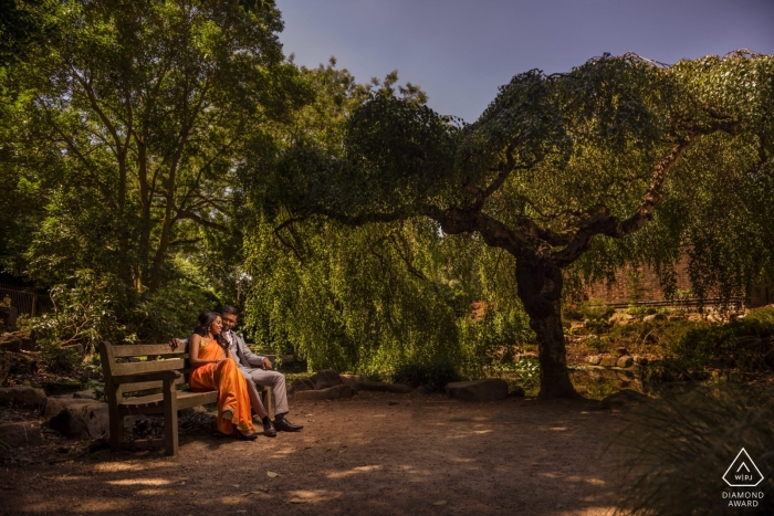 England engagement pictures of a couple sitting on a bench with nice tree shade  | UK photographer pre-wedding shoot with photographer