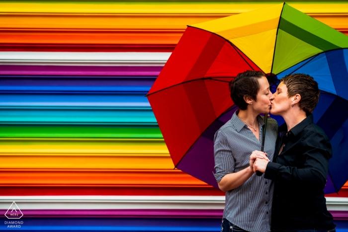 Ein Paar, das unter einem Regenbogenregenschirm, vor einem horizontalen gestreiften Regenbogenwandgemälde während ihrer Verlobungssitzung küsst