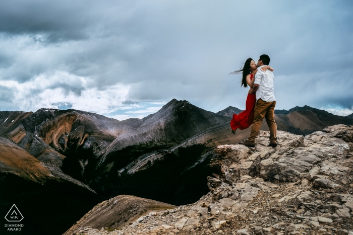 Canada mountain top pre-wedding engagement pictures of a couple in the wind | Alberta portrait shoot