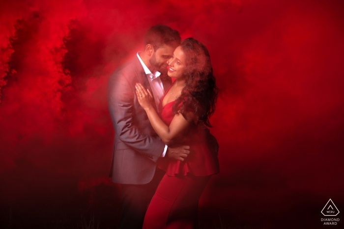 Essex pre-wedding engagement pictures of a couple - red dress and red smoke | UK couple photography session