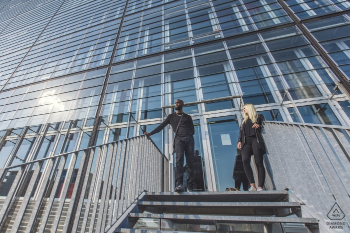 Haut-Rhin urban wedding engagement portrait of a couple on stairs with a huge glass building    Grand Estate pre-wedding photographer session
