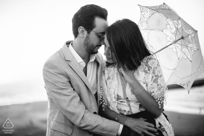 France black and white pre-wedding engagement pictures of a couple hugging with umbrella    Paris portrait shoot