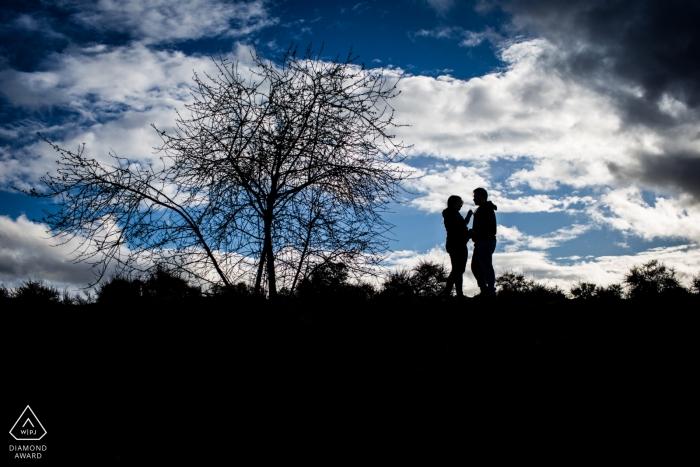 Photographie de fiançailles mariage Madrid avec un couple contre le ciel bleu avec des nuages | Photographie d'Espagne