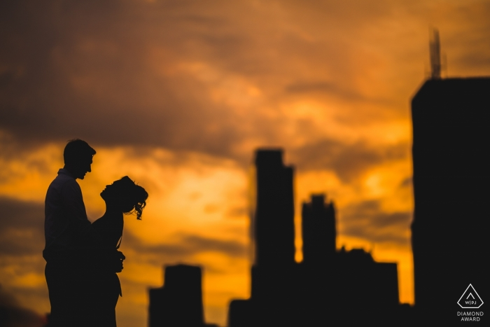 Night engagement pictures of a couple silhouetted before the city buildings  | DC photographer pre-wedding photo shoot session