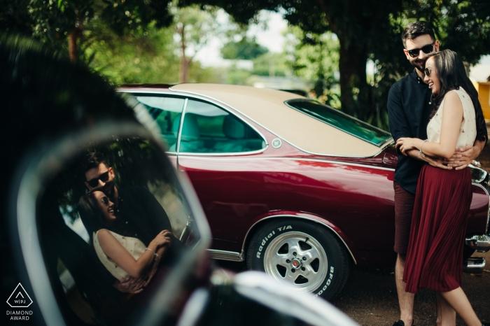 Photographe de mariage voiture Vintage hot rod | portrait de fiançailles d'un couple reflété dans un verre auto Photos de pré-mariage à Brasilia
