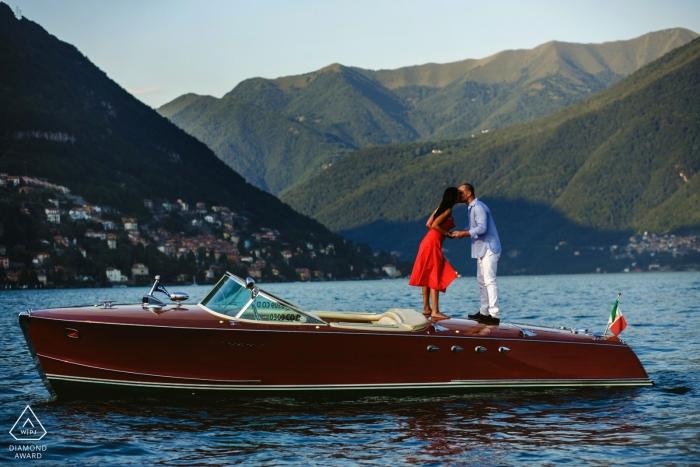 Tournage de photos de fiançailles au lac de Côme avec un couple s'embrassant dans un bateau