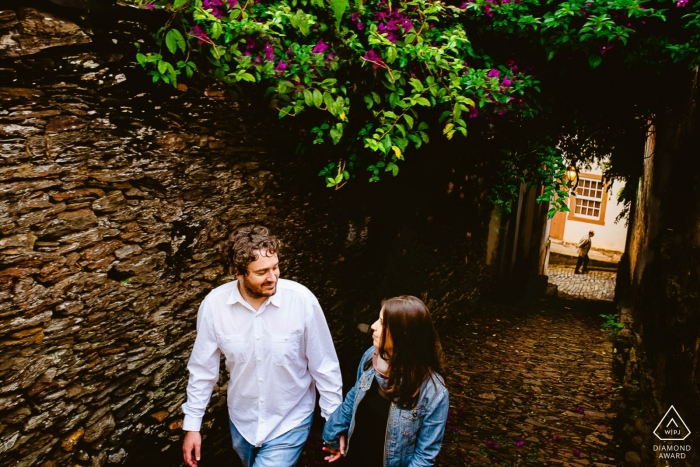 Walking engagement photos of a couple in town with stone walls | Minas Gerais photographer pre-wedding portrait session