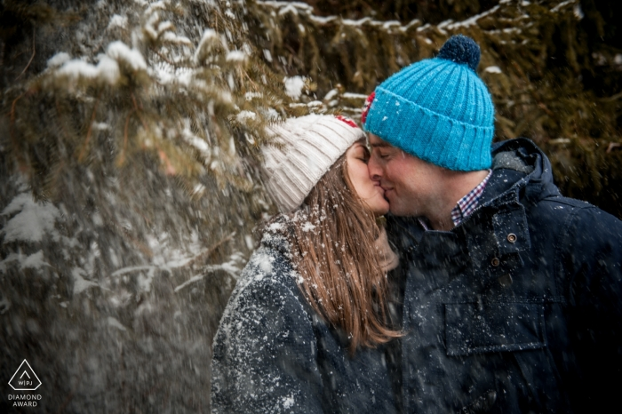 Engaged couple kissing in the snow covered trees | Séance engagement photo session - France