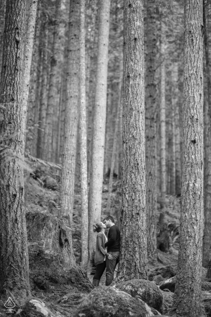 Vertical black and white portrait of engaged Seattle couple kissing