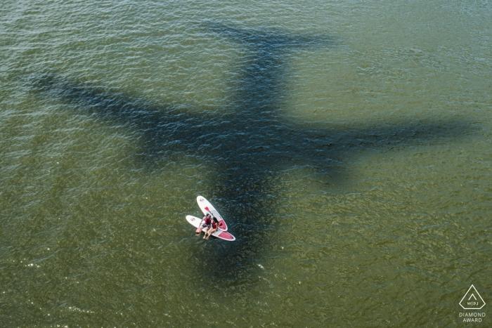 Fotografía de compromiso de boda SUP en District Of Columbia con la sombra de un avión en el agua