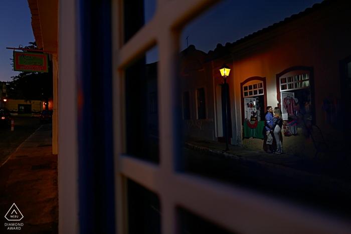 Engagement Portrait shot through glass windows in Goias