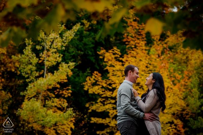 Verlobtes Paar kuscheln in Herbstfarben während ihrer Verlobungsfotosession Nelson BC Hochzeitsfotograf