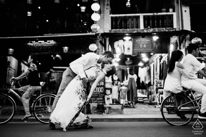 This engagement photo was taken at Hoi An of a couple dipping in the streets with bikes