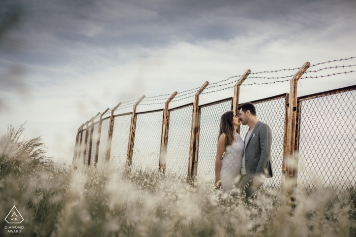 Love in front of the wire wall - Engagement Photograph with Barbed Wire topped Fence