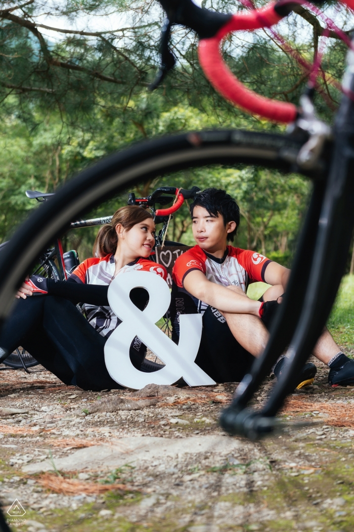 Taiwan Hualien Bicycle lovers - portrait of a young athletic couple through the spokes of a bike