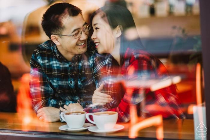 Ein frisch verlobtes Paar aus San Francisco genießt einen Moment gemeinsam in einem Café, während die Stadt sich in der Klasse vor ihnen widerspiegelt