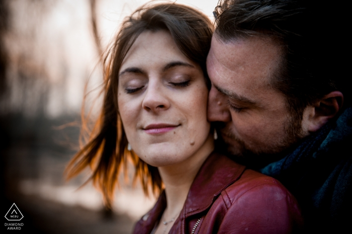 France engagement portrait with a woman closing her eyes as she is kissed on the neck by her fiancé