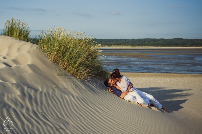 An Engaged Séance couple kiss on a wind swept Sand dune with sea grasses