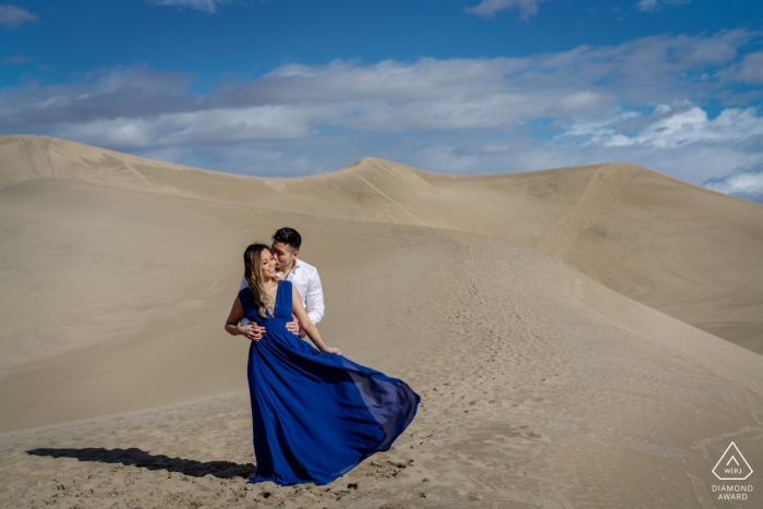 A couple hugs on the top of sand dunes for their engagement portrait in Death Valley