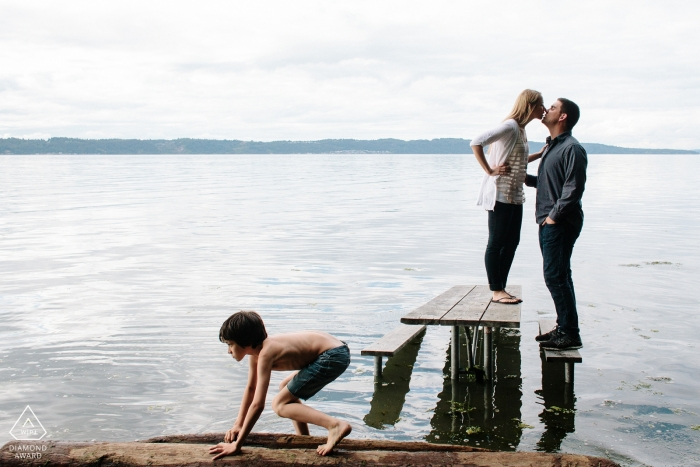 Creative Engagement Session Puget Sound - Couple kissing on picnic table in water