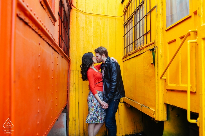 Creative Engagement Session Seattle - Bright colored trains surrounding kissing couple