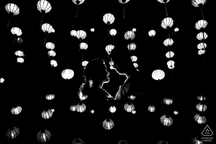 Hoi An black-and-white and portrait of a couple face-to-face below hanging lanterns