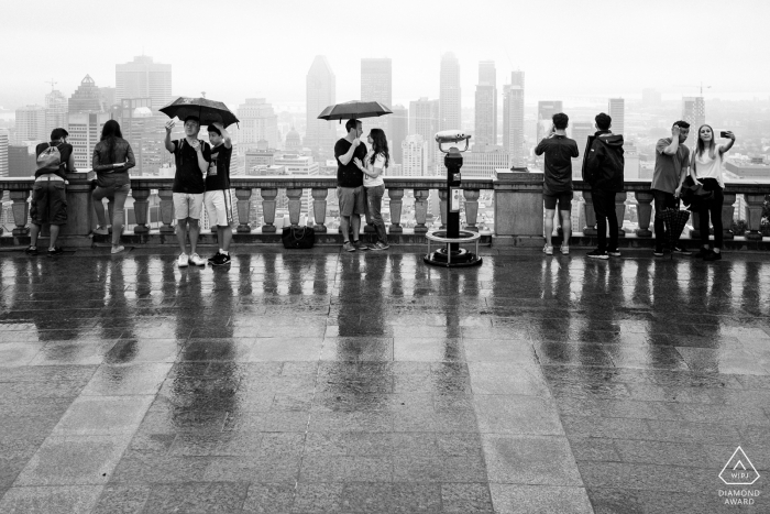 Black and white engagement photo in rain at Mount Royal belvedere