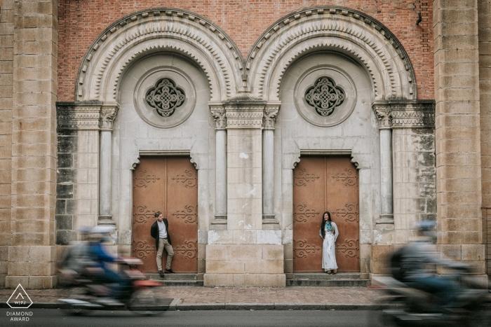 Sai Gon Verlobungsportrait eines Paares, das in separaten Türöffnungen steht, während Roller vorbeifahren