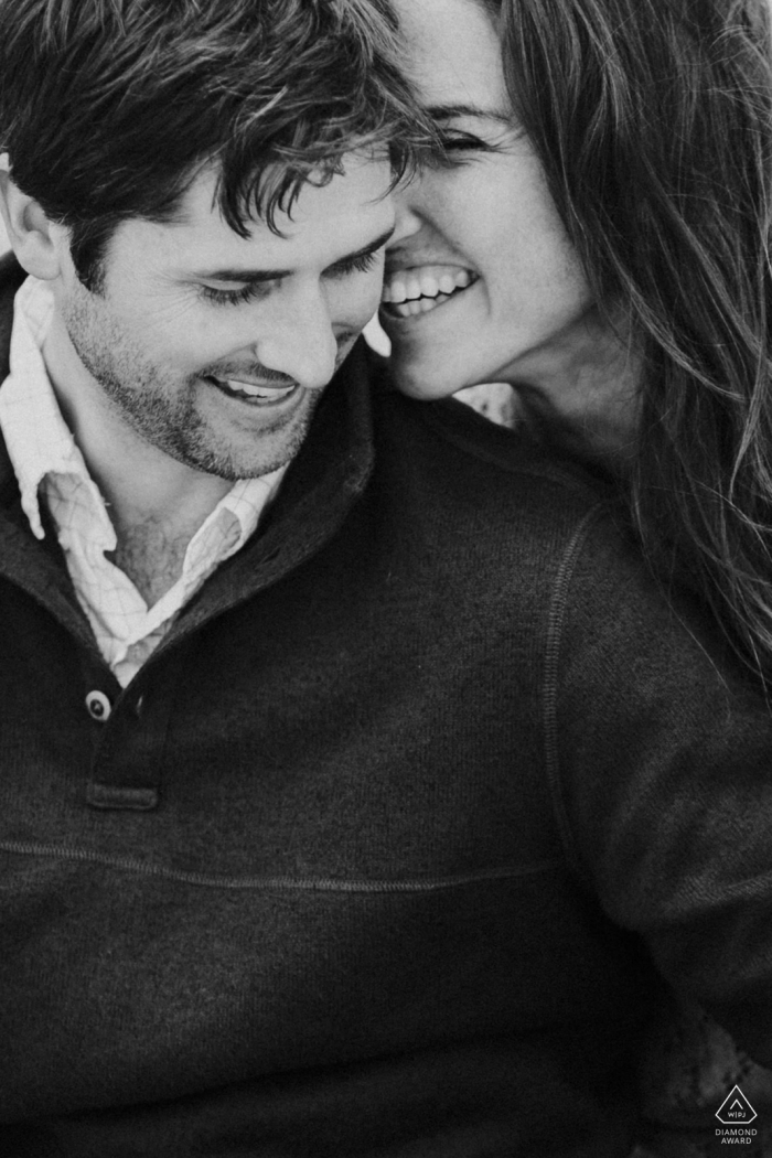 Vertical portrait of a young newly engaged couple laughing in black-and-white
