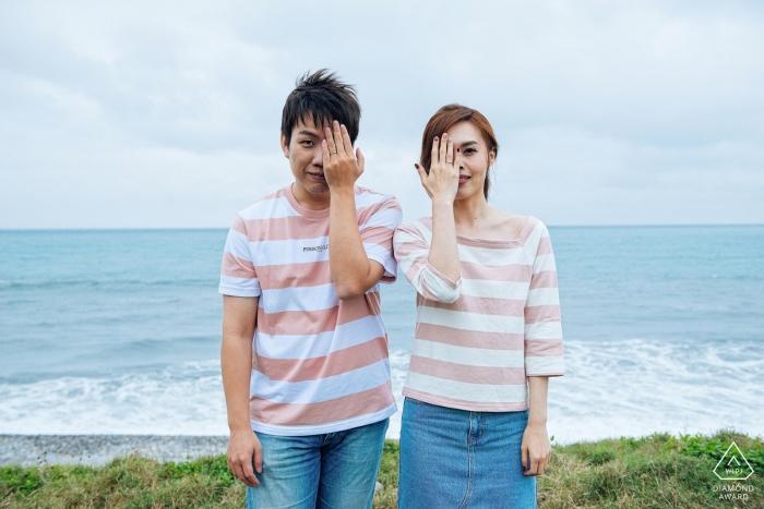 台灣,花蓮在海灘對稱訂婚肖像| 他們每人用手遮住一隻眼睛