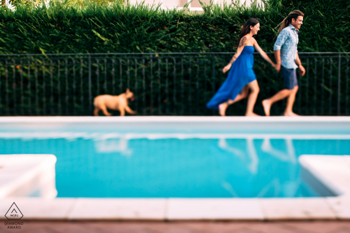 Acqui Terme (Alessandria), Piemonte, Italia pre-wedding portrait photographer - Couple running around the swimming pool with a dog