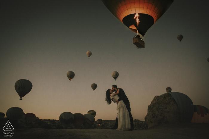 Portraits de fiançailles en Cappadoce d'un couple s'embrassant sous des montgolfières