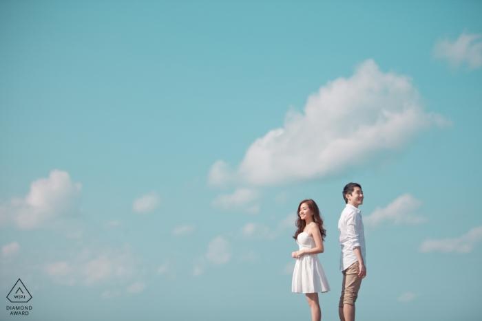 Jeju, Korea couple shooting pre-wedding portraits with a blue sky and clouds