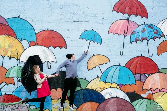 Tacoma, Washington Fotosession   verlobt paar springen mit wand von sonnenschirmen