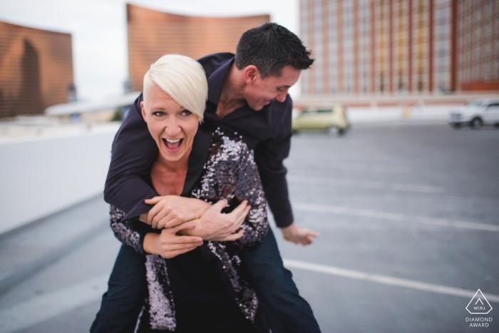 Las Vegas Verlobungsporträts auf dem Hotelparkplatz | Let's Ride - sie fährt ihn huckepack in die Stadt