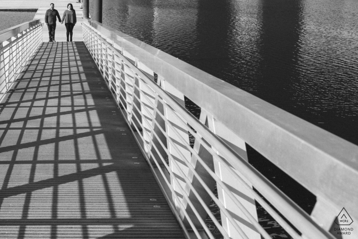 Tacoma, Washington engagement portraits of a Couple holding hands on dock   shadows and lines frame this engaged couple showing the light and darkness they came through to be together