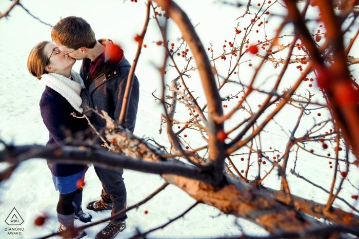 Tenney Park, Madison, Wisconsin portraits de pré-mariage | Les fiancés prennent un moment pour s'embrasser en marchant sur le brise-lames enneigé du lac Mendota.