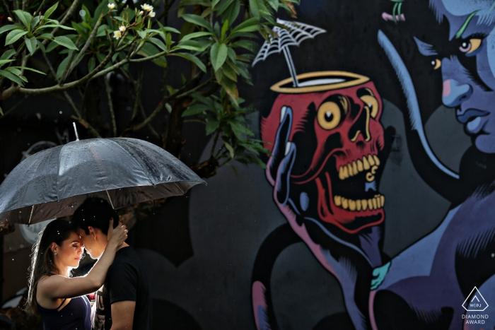 Diablo Pub Pré-mariage séance de portrait de couple avec une lumière, un parapluie et des peintures murales de graffitis sur le mur