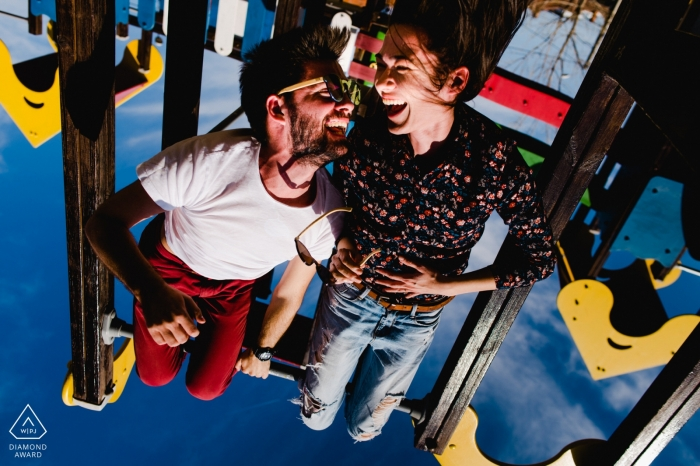 Playground in Timisoara, Romania pre-wedding portrait session | Hanging on the playground gears upside down.