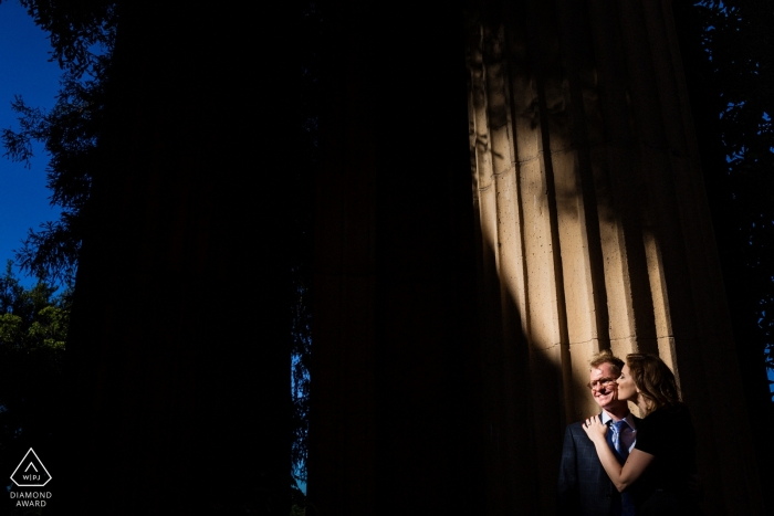 A small shaft of sunlight illuminates this couple as they embrace for their San Francisco engagement portraits