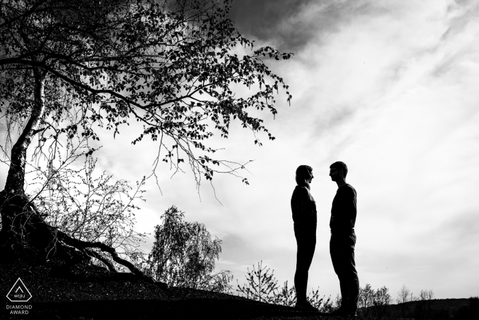 Black and white engagement photo of a couple silhouetted outside in Aachen.
