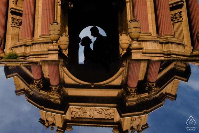 Photo d'engagement d'un couple dans le reflet d'un immeuble à San Francisco.