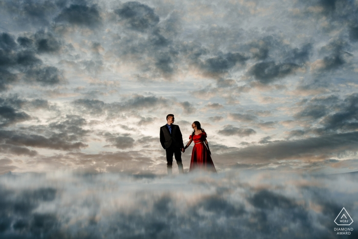 Engagement photo of a couple made to look as if they are standing on clouds in San Francisco.