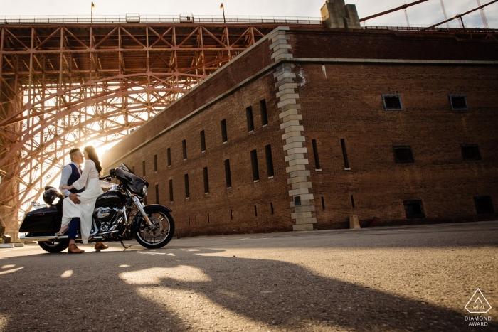 Séance photo de fiançailles d'un jeune couple assis sur une moto devant un bâtiment en brique à San Francisco.
