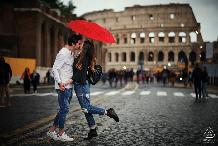 A loving engagement portrait of a couple kissing under a red umbrella in front of the Colosseum in Rome, Italy.