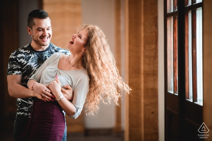 Engagement photo of a young couple in love and laughing while they dance indoors in Ruse, Bulgaria.