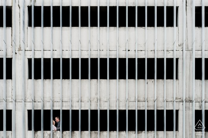 Engagement photo of a couple standing in a white building with large, vertical beams in Agen, France.